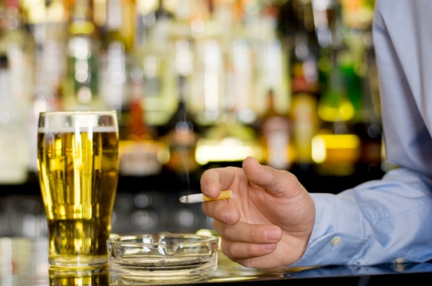 Man in a bar with a pint of beer smoking a cigarette
